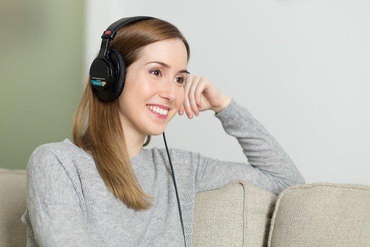 Frau lernt glücklich über Kopfhörer