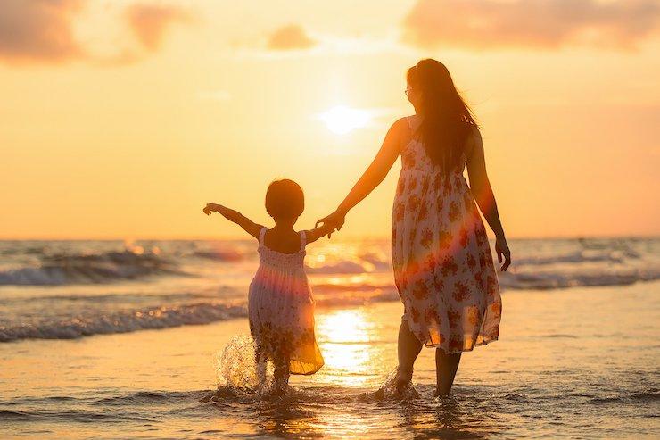 Au-Pair passt auf Kind am Strand auf